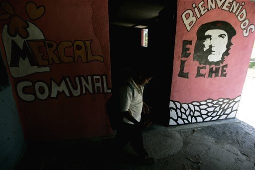In this photo taken on April 2, 2009, a boy walks next to a state owned market at the expropriated cattle ranch El Charcote, in Venezuela's Cojedes state. (AP Photo/Fernando Llano)