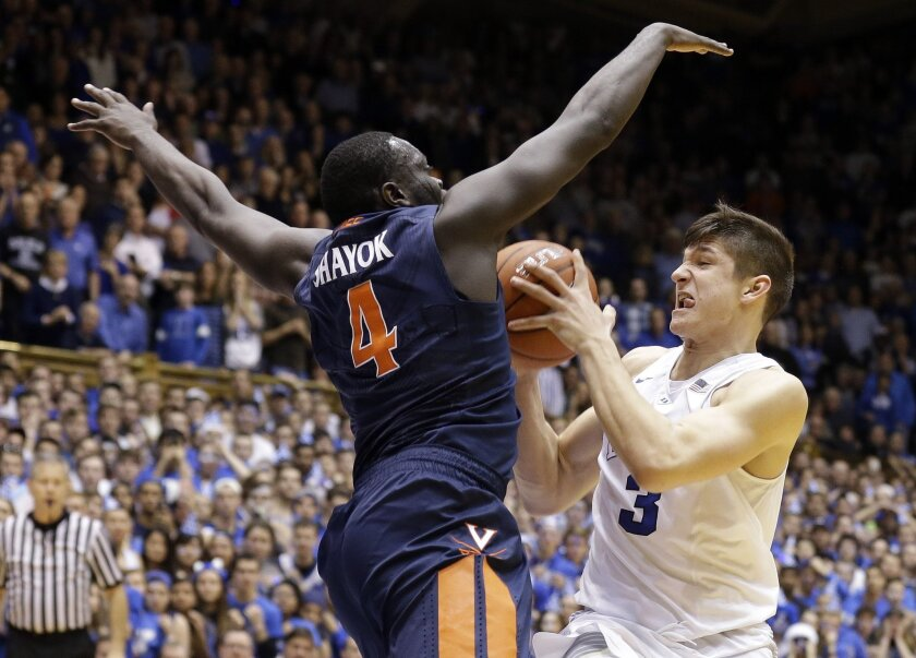 Duke's Grayson Allen (3) drives to the basket against Virginia's Marial Shayok (4) during the second half of an NCAA college basketball game in Durham, N.C., Saturday, Feb. 13, 2016. Allen scored on the play to give Duke the victory 63-62. (AP Photo/Gerry Broome)