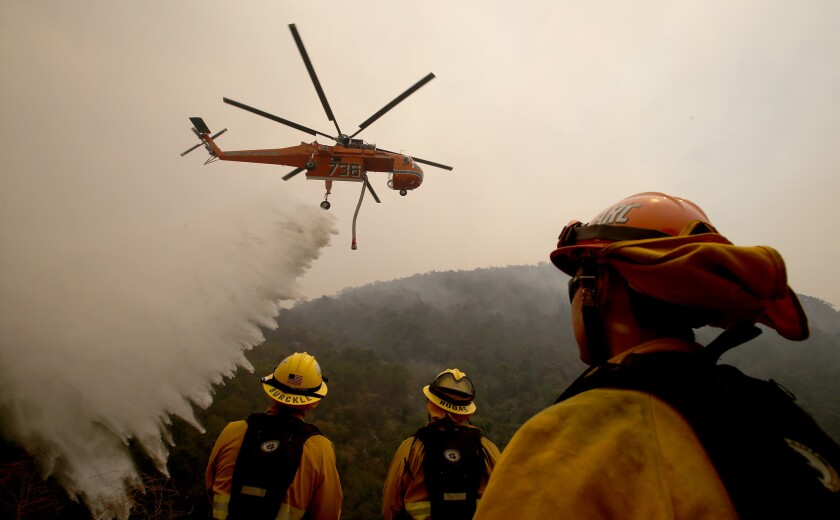 A helicopter drops water on the Alamo fire near Santa Maria on Saturday.