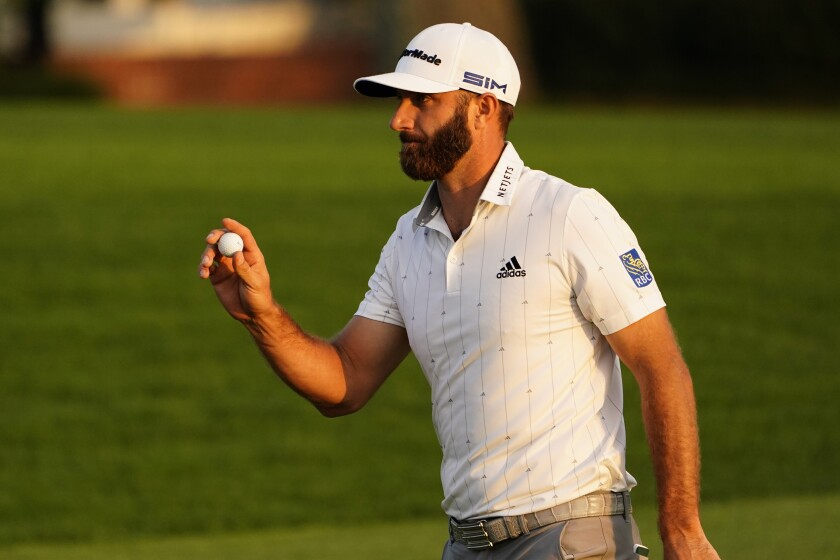 Dustin Johnson holds up his ball on the 18th green after finishing the third round of the Masters on Saturday.