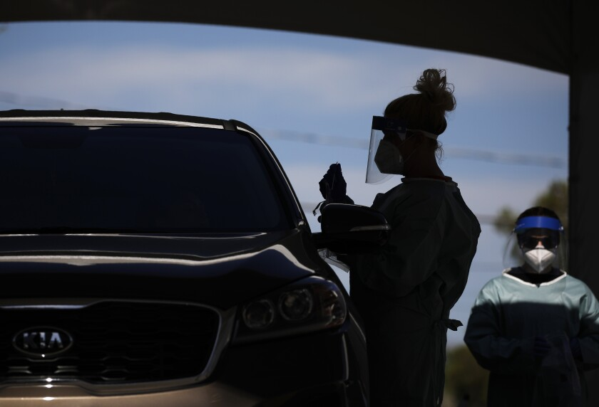 Healthcare workers test patients in their cars in Las Vegas.