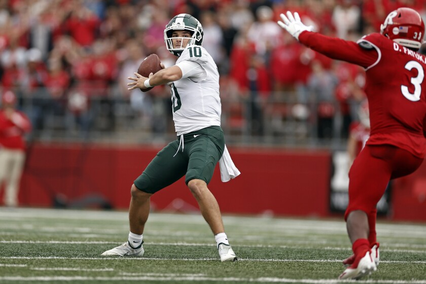 Michigan State quarterback Payton Thorne (10) passes under pressure from Rutgers linebacker Olakunle Fatukasi (3) during the first half of an NCAA college football game Saturday, Oct. 9, 2021, in Piscataway, N.J. (AP Photo/Adam Hunger)