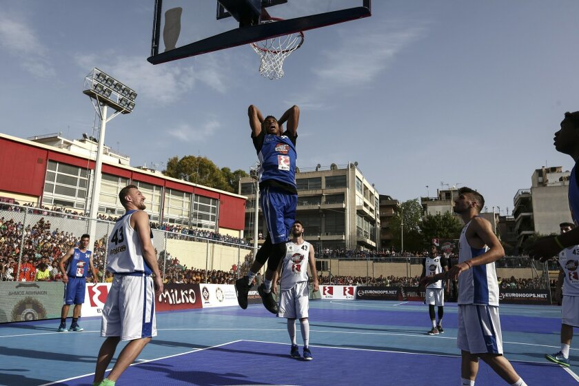 Milwaukee Bucks' forward Giannis Antetokounmpo, center, jumps to dunk the ball during a friendly game in Athens, on Sunday, May 29, 2016. New York Knicks star Kristaps Porzingis joined fellow NBA player Giannis Antetokounmpo, of the Milwaukee Bucks, and his older brother Thanasis, for a game of str