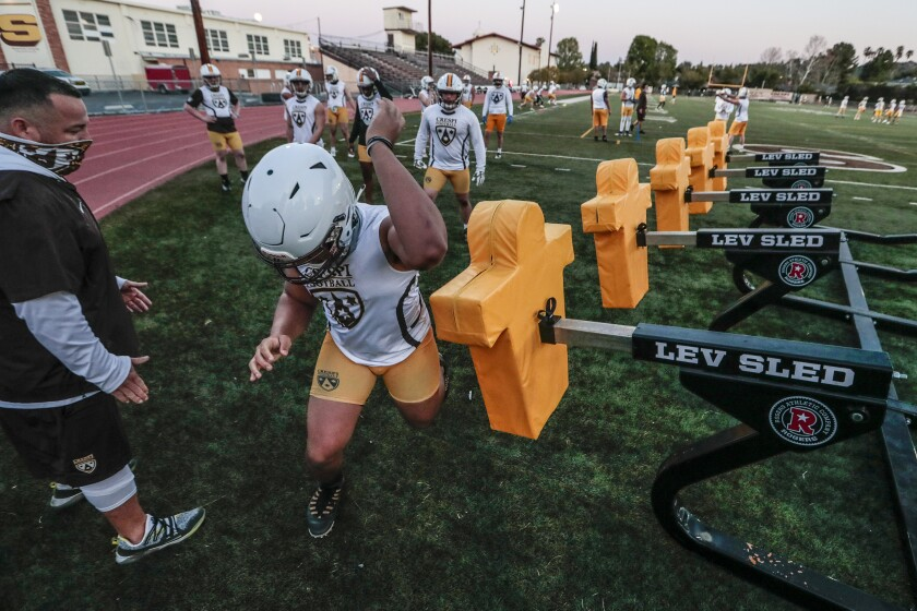 Crespi High football players practice on the field.