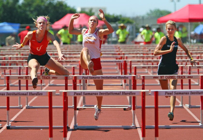 Hannah Labrie-Smith of Cathedral Catholic, center, has trouble with a hurtle as she finishes 5th between first place finisher Leah Molter of Valhalla, left, and 2nd place finisher Hannah Nealis of Valley Center, right, in the 100 meter hurdles Saturday during the Mt. Carmel Invitational. photo by B
