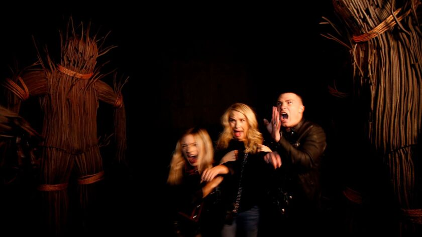 """""""American Horror Story"""" actors Billie Lourd, left, Leslie Grossman and Colton Haynes react to a few of the surprises at the American Horror Story: Roanoke attraction at Universal Studios."""