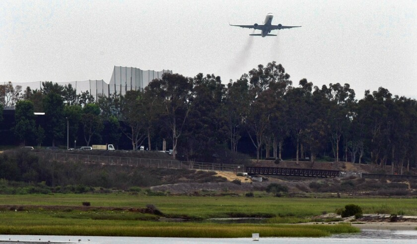 A commercial jet leaves John Wayne International Airport and flies over the Upper Newport Bay.