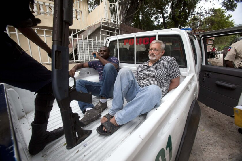 FILE - In this Friday, Sept. 5, 2014, file photo, U.S. citizen Michael Karl Geilenfeld waits in handcuffs as the manager of his orphanage sits with him in the back of a police truck outside the St. Joseph's Home For Boys after police closed it down in the Delmas area of Port-au-Prince, Haiti. A jud