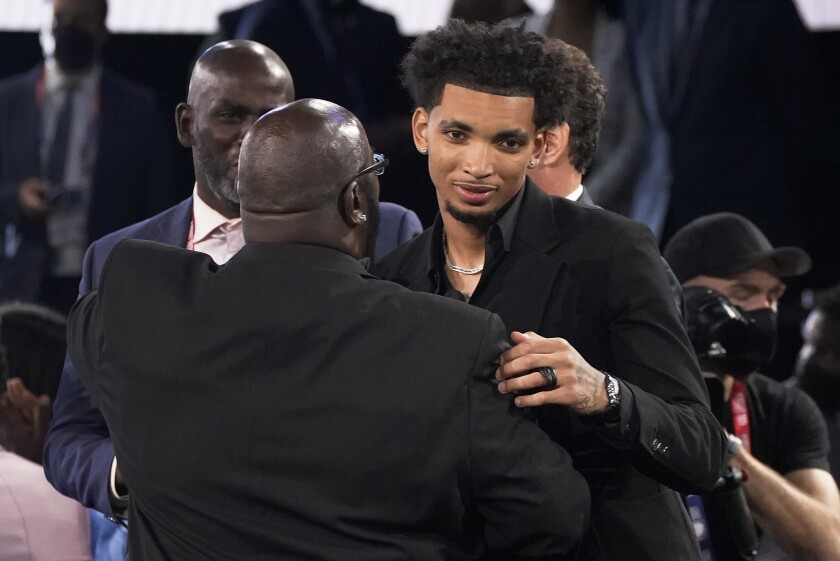 James Bouknight, right, reacts after being selected 11th overall by the Charlotte Hornets during the NBA basketball draft, Thursday, July 29, 2021, in New York. (AP Photo/Corey Sipkin)