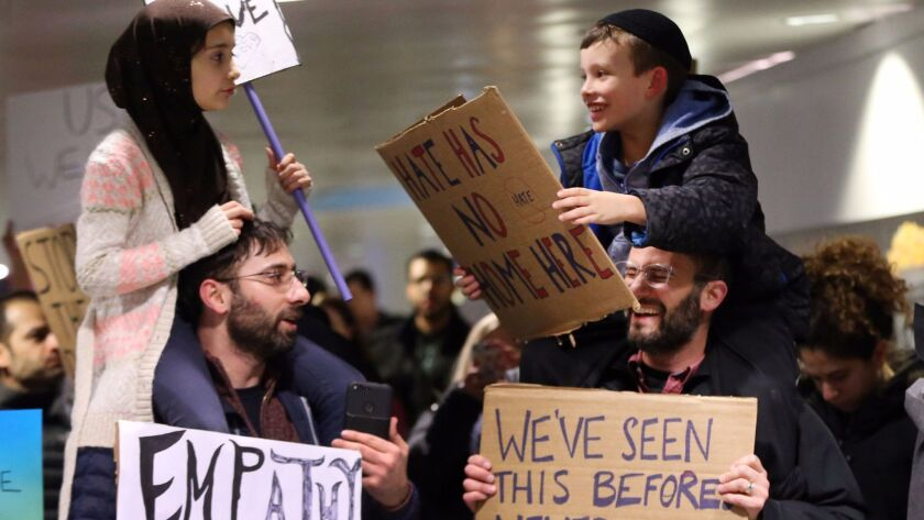 Meryem Yildirim, 7, left, sits on her father, Fatim, of Schaumburg, Ill., and Adin Bendat-Appell, 9, right, sits on his father, Rabbi Jordan Bendat-Appell, of Deerfield, Ill., during a protest on Jan. 30 at O'Hare International Airport in Chicago.