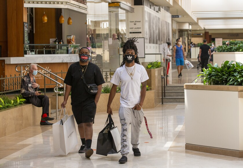 Jeff Luckey, left, and Tarique Lusk shop during the reopening of South Coast Plaza on Monday in Costa Mesa.