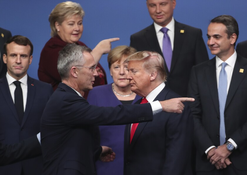 FILE - In this Dec. 4, 2019, file photo, NATO Secretary General Jens Stoltenberg, center front left, speaks with U.S. President Donald Trump, center front right, after a group photo at a NATO leaders meeting at The Grove hotel and resort in Watford, Hertfordshire, England. For America's allies and rivals alike, the chaos unfolding during Donald Trump's final days as president is the logical result of four years of global instability brought on by the man who promised to change the way the world viewed the United States. (AP Photo/Francisco Seco, File)