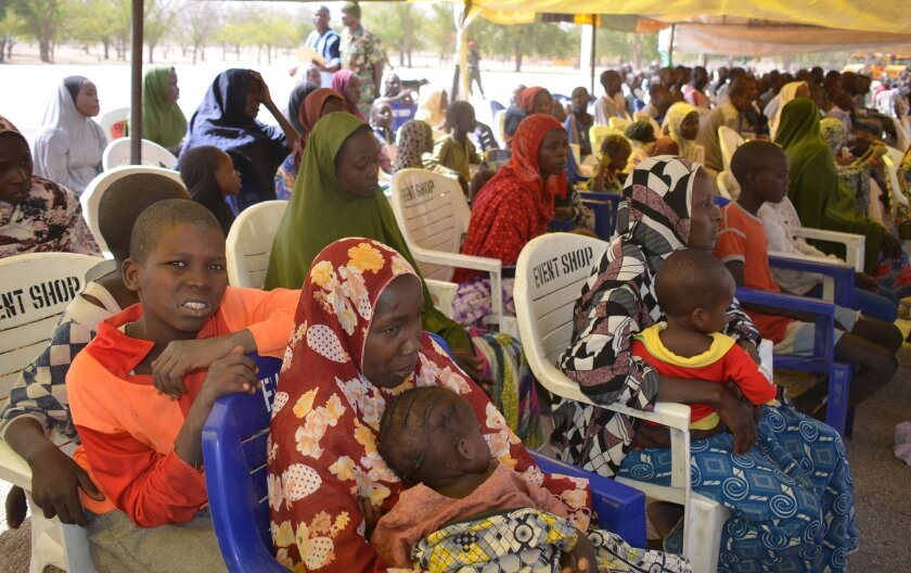 woman and children detained by Nigeria army who has no links to Boko Haram sits under a canopy before their release at the Military barracks in Maiduguri , Nigeria, Friday Feb. 12, 2016. Nigeria's army freed 267 detainees Friday including dozens of minors, some looking no more than 3-years old, say