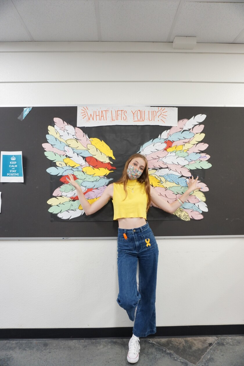 """Senior Mirabel Hunt in front of the """"What Lifts You Up?"""" wings"""