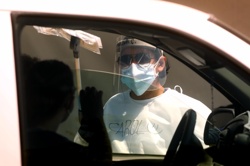 A healthcare worker passes a COVID-19 self-test kit to a participant in a car at a test site.