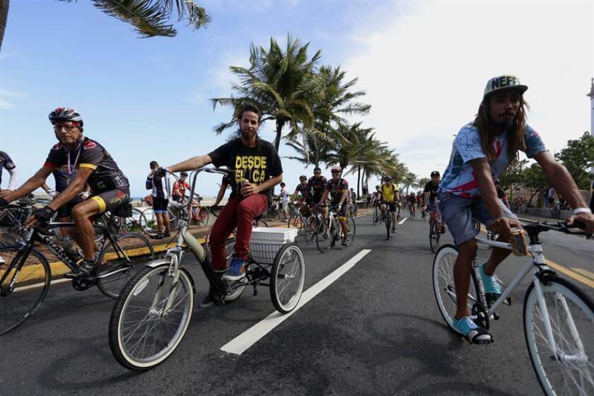 """Ciclistas participan en la bautizada """"Bici-Marcha"""" hoy, domingo 8 de diciembre de 2013, en San Juan (Puerto Rico). Cientos de ciclistas recorrieron las principales avenidas de la ciudad para reclamar más seguridad en las calles de Puerto Rico y el fin a las muertes de aficionados a este deporte y medio de transporte en las carreteras de la isla caribeña. EFE/Thais Llorca"""