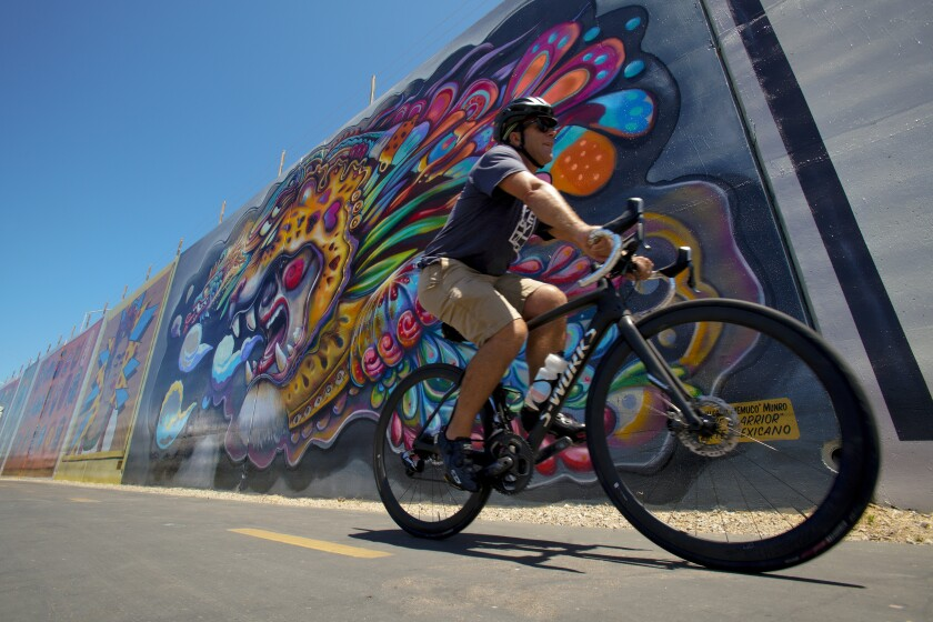 Andy Hanshaw rides past a mural along the Bayshore Bikeway in Chula Vista in 2019.