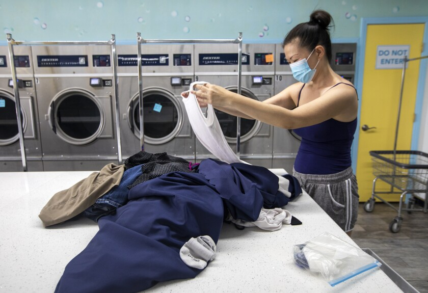 A woman in a mask folds clothes on a counter in a laundromat