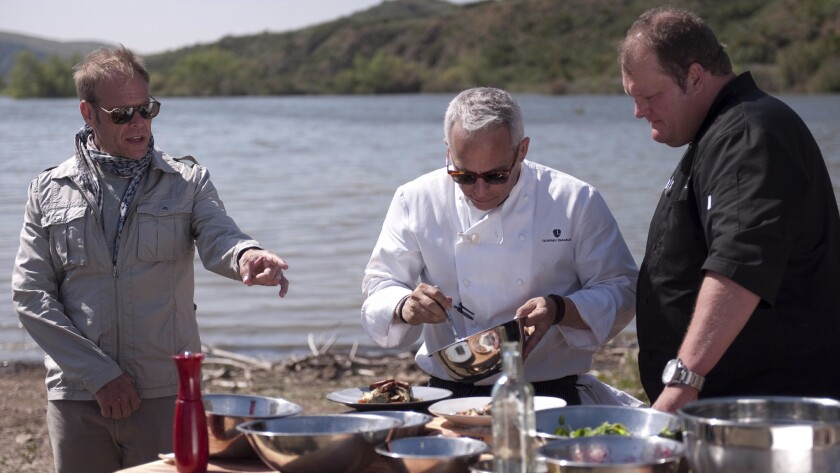 """Chef Geoffrey Zakarian, center, prepares a dish during an episode of the Food Network show """"The Next Iron Chef."""""""