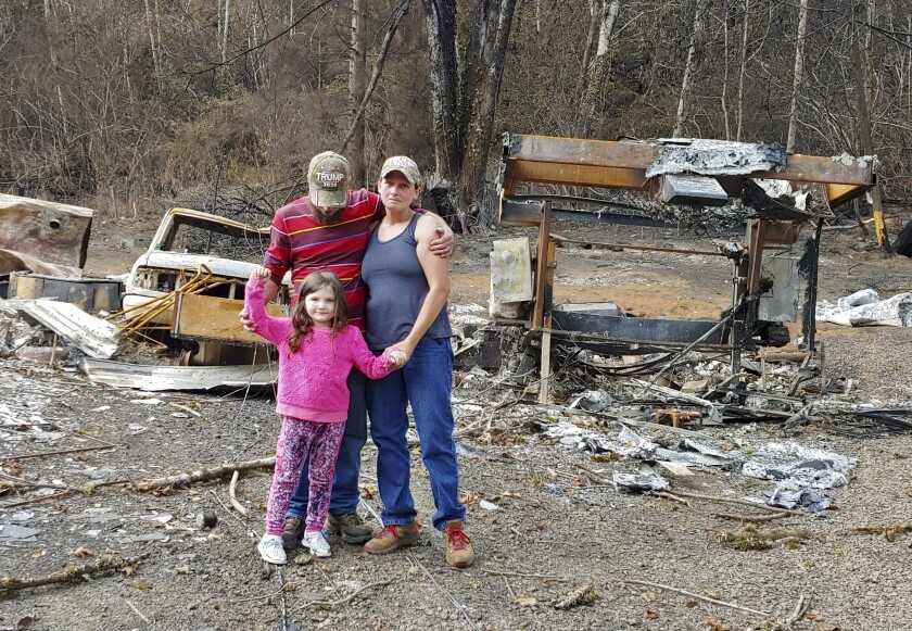 Tye and Melynda Small standing with their 5-year-old daughter, Madalyn, amid the ruins of their home in Otis, Oregon