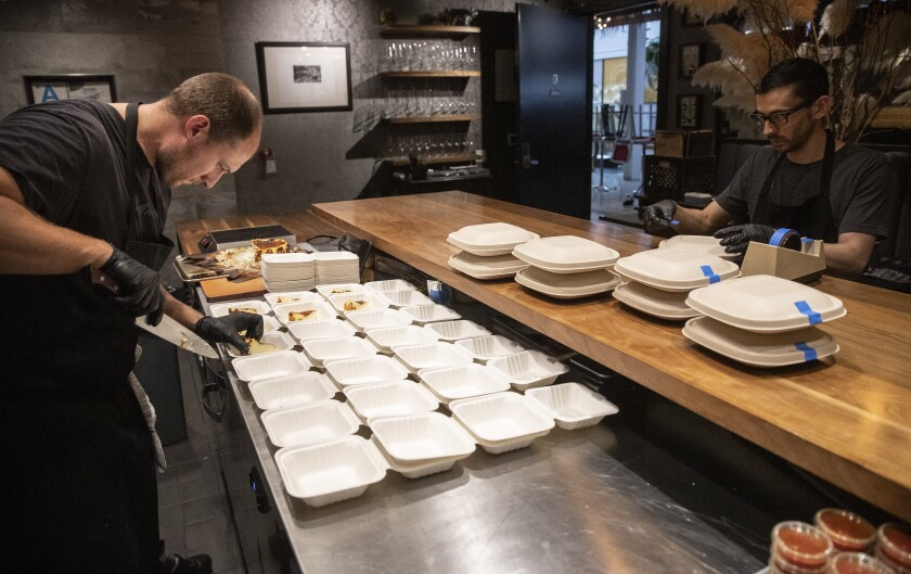 Dave Beran slices Basque cheesecake, left, at his Santa Monica tasting-menu restaurant Dialogue as cook David Olvera packages its new three-course, $35 takeout meals.