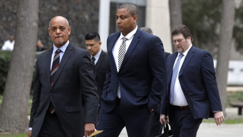 Jonathan Martin, center, walks with his attorney Winston McKesson, left, to be booked at the Los Angeles Police Department after pleading not guilty to making criminal threats at the Van Nuys Courthouse on Tuesday.