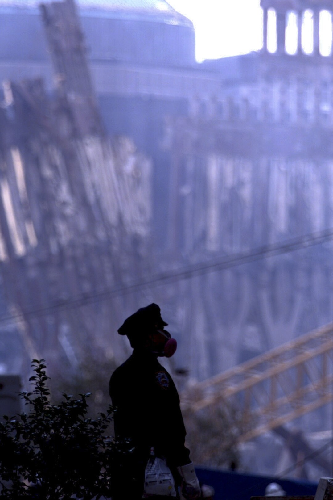 A policeman wearing a gas mask is silhouetted against the remains of a building