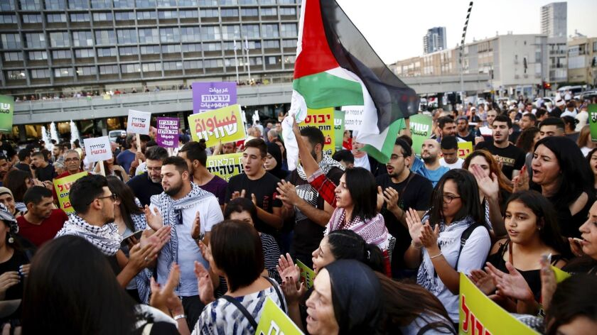 Israeli Arabs hold a Palestinian flag during a protest against the Jewish nation bill in Tel Aviv, I