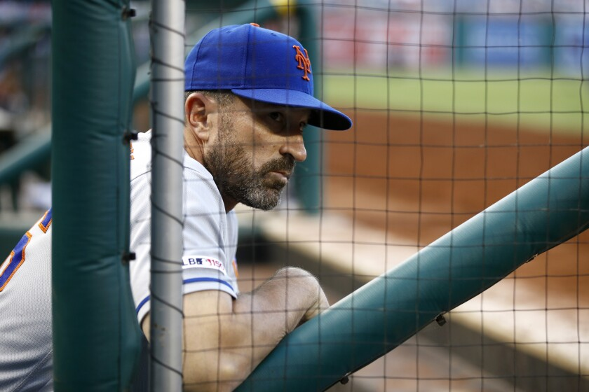 New York Mets manager Mickey Callaway leans in the dugout