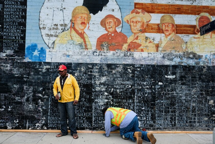 Former U.S. Marine Jon Scudder, left, watches as a Metropolitan Transit Authority worker prepares to cover a vandalized Vietnam War Memorial in the Venice area of Los Angeles on Monday, May 30, 2016. The Los Angeles memorial honoring prisoners and those missing in action during the Vietnam War has