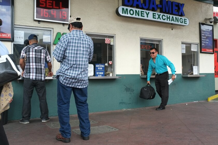 In this file photo, Aroon Dominguez, right, picks up his bag after exchanging pesos for dollars after crossing into the U.S. from Mexico at the San Ysidro border crossing. Dominguez was one of six people who was allowed to return to the U.S. as part of a class action suit by the ACLU that claims certain undocumented immigrants had been coerced into signing voluntary repatriation forms after being detained by U.S. immigration officials. Dominguez had been returned to Mexico in 2011..Photo - David Maung.