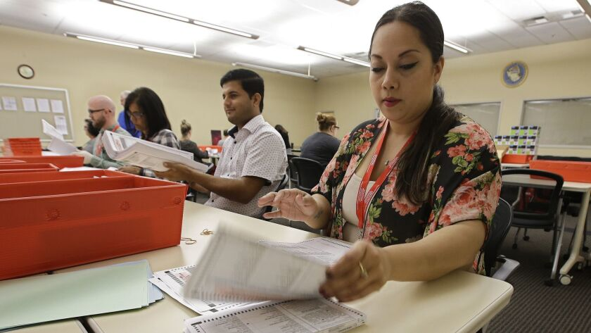 Bianca Savola, an election clerk at the Sacramento County Registrar of Voters, inspect a mail-in bal