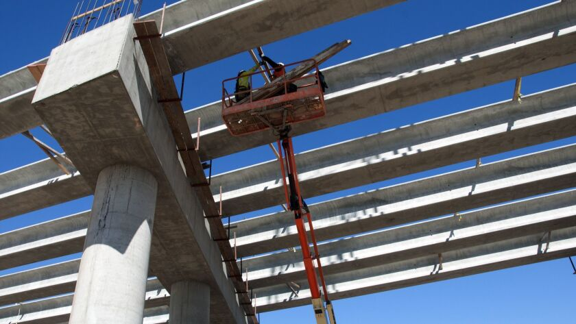 Crews stabilize the recently placed girders at the Avenue 12 overcrossing on bullet train constructi