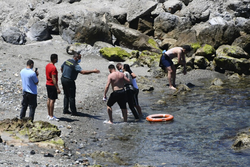 A woman from Morocco gets help from some men to get out of the water and onto the beach