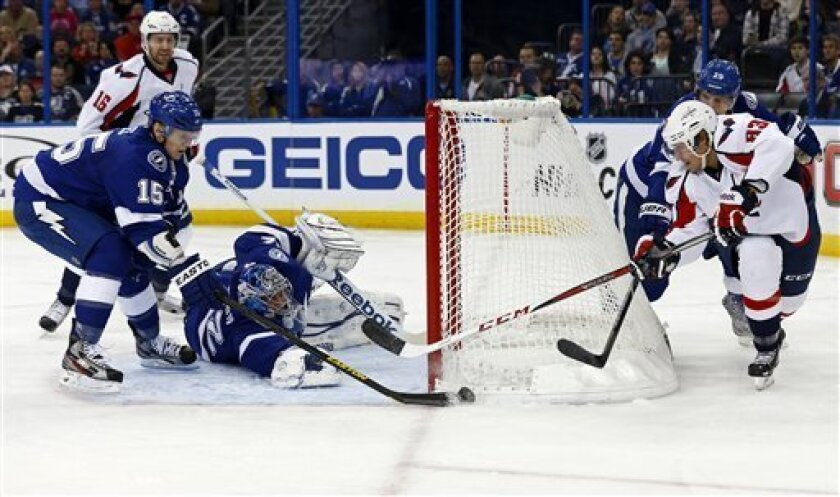 Tampa Bay Lightning defenseman Brian Lee (15) deflects a wraparound-attempt by Washington Capitals' Jay Beagle in front of goalie Mathieu Garon during the first period of an NHL hockey game on Thursday, Feb. 14, 2013, in Tampa, Fla. (AP Photo/Mike Carlson)