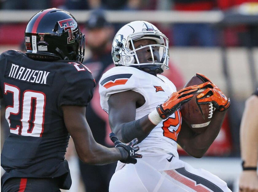 Oklahoma State wide receiver James Washington right, takes a J.W. Walsh pass into the end zone for a touchdown in front of Texas Tech defensive back Tevin Madison (20) in the fourth quarter of an NCAA college football game in Lubbock, Texas, Saturday, Oct. 31, 2015. Oklahoma State won 70-53. (AP Ph