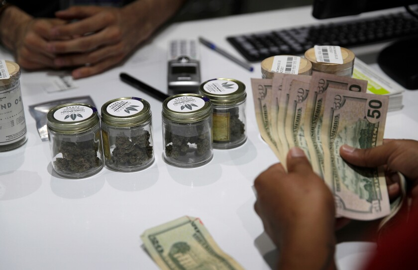FILE - In this July 1, 2017, file photo, a person buys marijuana at the Essence cannabis dispensary