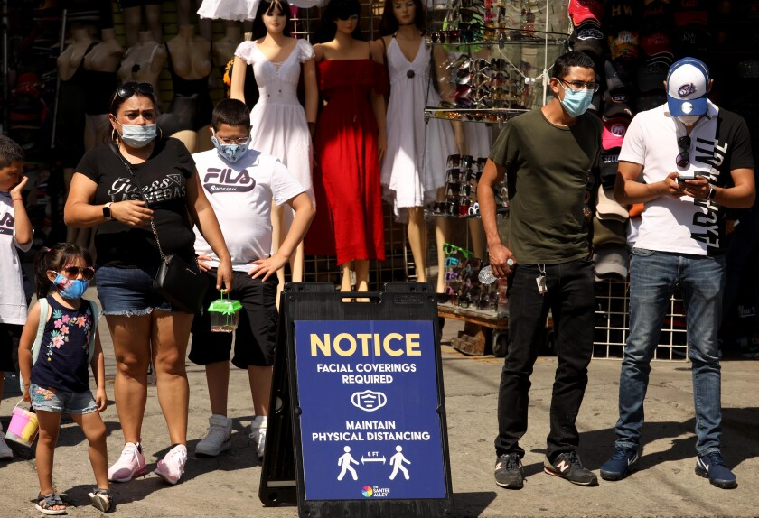Shoppers wear masks while walking along Santee Alley in the Garment District in downtown Los Angeles.