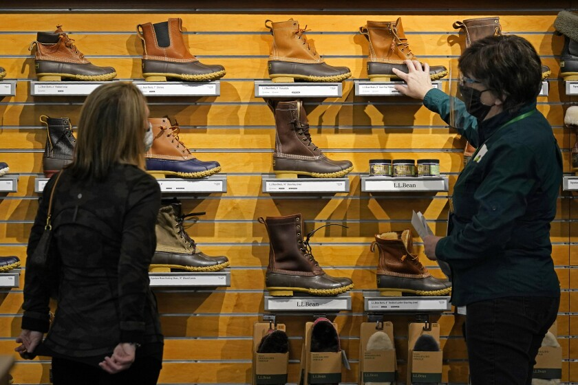 FILE - In this March 18, 2021 file photo, a salesperson helps a customer shopping for Bean Boots at the L.L. Bean flagship retail store in Freeport, Maine. Newly vaccinated and armed with $1,400 stimulus checks, Americans went on a spending spree last month, buying new clothes and going out to eat again. Retail sales surged a seasonally adjusted 9.8% after dropping about 3% the month before, the Commerce Department said Thursday, April 15. (AP Photo/Robert F. Bukaty, File)