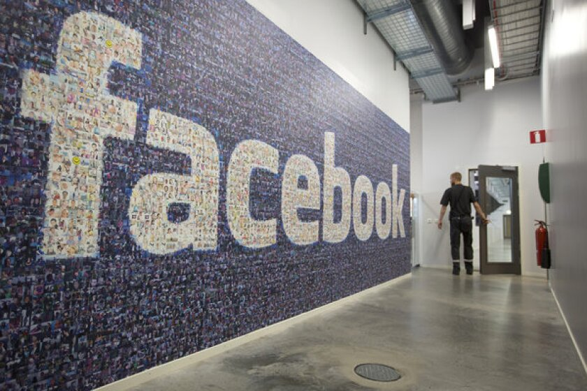 A wall covered with the Facebook logo