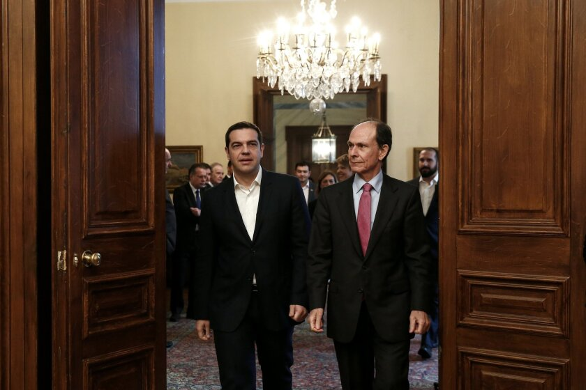 Greece's Prime Minister Alexis Tsipras, left, is escorted by an official of the Presidential palace as he arrives for a meeting of the Greek political party leaders in Athens, Saturday, Nov. 28, 2015. Tsipras called on the leaders of Greek opposition parties to hold an emergency meeting this weekend to seek consensus on the pension reform. (AP Photo/Yorgos Karahalis)