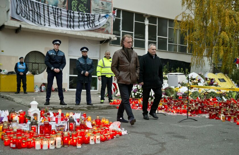 Dutch violinist and conductor Andre Rieu, center left, walks after laying flowers outside the Colectiv nightclub in Bucharest, Romania, Saturday, Nov. 7, 2015. Seven more people have died a week after a fire broke out in a Bucharest nightclub. About 100 other people still remain hospitalized, of wh