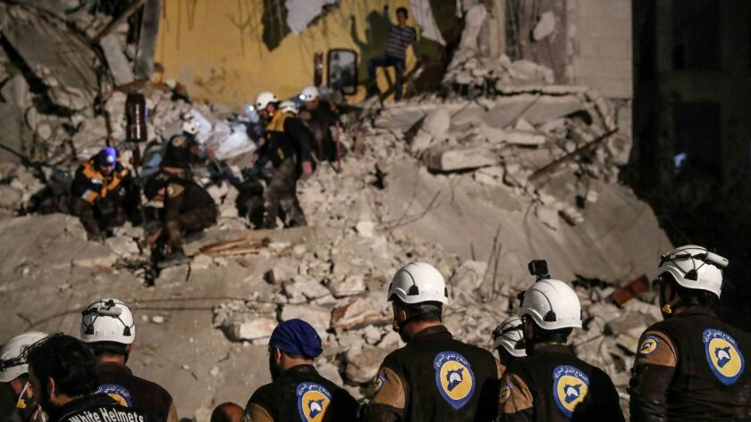 White Helmets volunteers search for survivors after an explosion in Idlib, Syria, on April 9. Hundreds of the Syrian rescue workers stranded along the frontier with the Israeli-occupied Golan Heights have been evacuated.