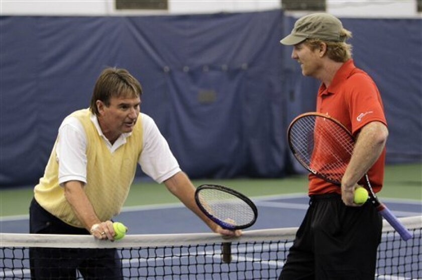 Jimmy Connors, left, and Jim Courier talk at the Billie Jean King National Tennis Center during the U.S. Open tennis tournament in New York, Wednesday, Sept. 7, 2011. (AP Photo/Mike Groll)