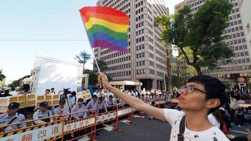 A man waves a rainbow flag during a protest outside Taiwan's parliament in Taipei on Nov. 17, 2016.