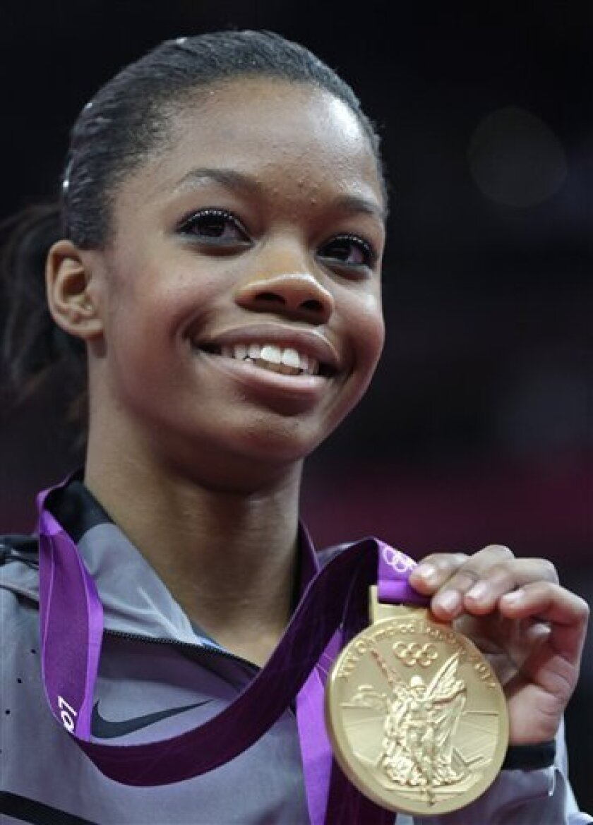 U.S. gymnast Gabrielle Douglas displays her gold medal during the artistic gymnastics women's individual all-around competition at the 2012 Summer Olympics, Thursday, Aug. 2, 2012, in London. (AP Photo/Julie Jacobson)