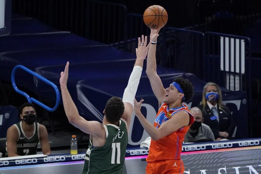 Oklahoma City Thunder forward Justin Jackson, right, shoots in front of Milwaukee Bucks center Brook Lopez (11) in the first half of an NBA basketball game Sunday, Feb. 14, 2021, in Oklahoma City. (AP Photo/Sue Ogrocki)