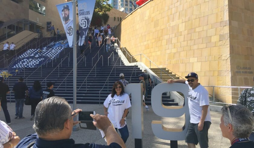 David and Virginia De La Cruz of Murrieta get their picture taken standing next to Tony Gwynn's No. 19 at the entrance to Petco Park.