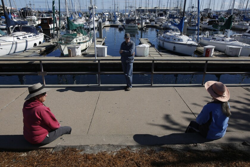 Terry Hanna, left, her husband, Mike, and Melanie Cervi practice social distancing Tuesday near Fisherman's Wharf in Monterey, Calif.