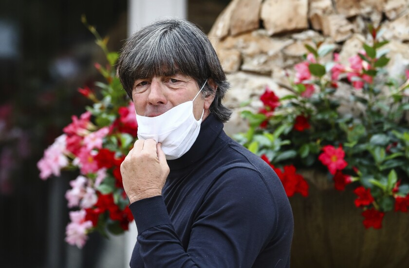 German national soccer team coach Joachim Loew takes off his mask as he arrives at the Wald-Hotel in Stuttgart, Germany, Monday, Aug. 31, 2020. Germany will play against Spain in the UEFA Nations League on Thursday, Sept. 3, 3030 in Stuttgart. (Christoph Schmidt/dpa via AP)